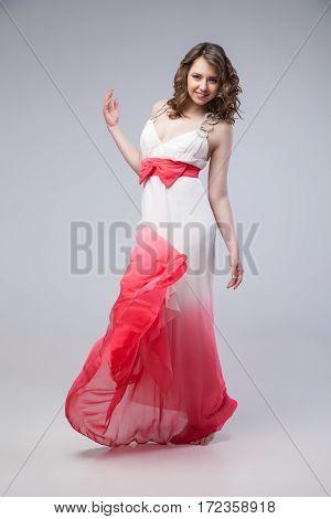 Elegant girl in fluttering dress posing at studio