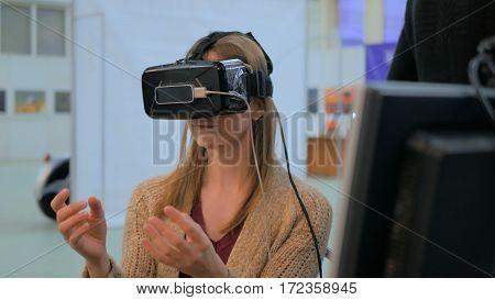 Virtual reality game. Young woman using virtual reality glasses. VR