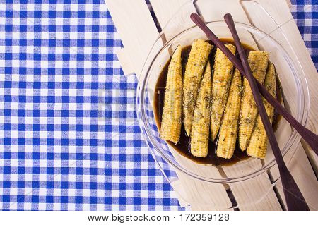Baby corn with soy marinade of soy sauce rosemary olive oil and garlic on the blue tissue