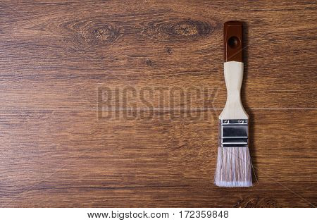 paint brush lying on a wooden background, brown grunge texture