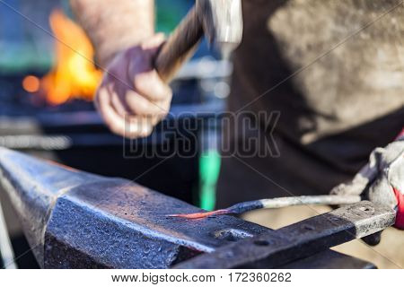 Blacksmith hammering red hot iron rod on anvil against the background of fire