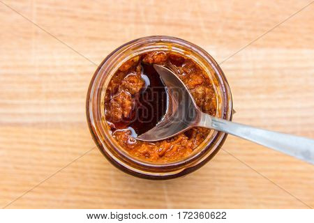 spoon in glass jar of red pesto rosso