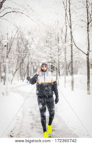 Jogger / sportsman using cellphone in cold weather.