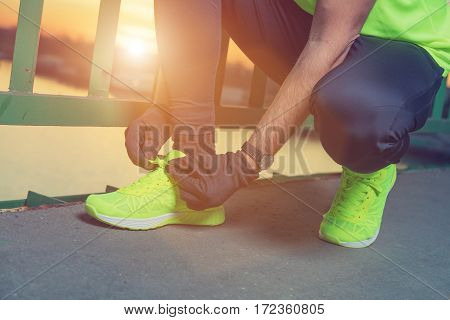 Urban jogger tying running shoes on the bridge.