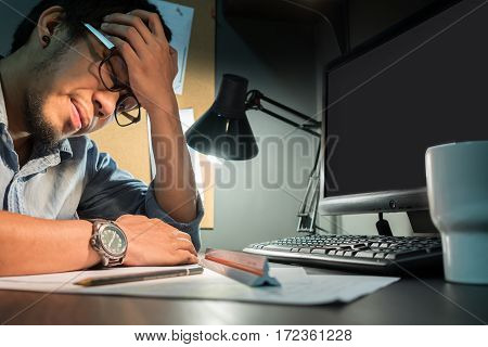 Asian man feeling exhausted. Young beard man wear eyeglasses having headache while sitting at his working. Stressed depressed thinking.