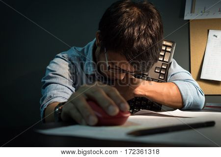 Feeling tired. Creative editor holding keyboard and mouse of computer while sleeping on office desk. Asian creative editor wear eyeglasses fall asleep.