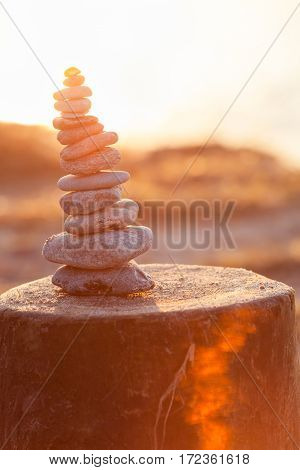 Tower of pebbles with shell on top at bright evening sunshine, built on wooden groin