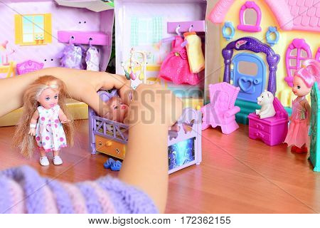 Little girl playing with dolls. Girl lays a doll down to sleep on a bed. Colorful toy set on a table. Funny game to develop kids imagination and life skills