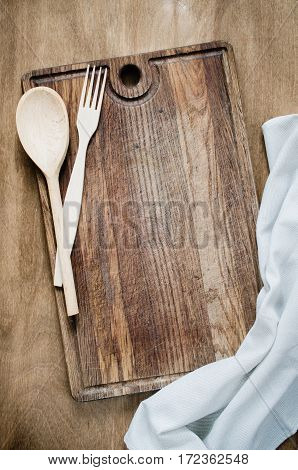 Kitchen Background: Rustic Cutlery with Kitchen Towel or Napkin on Wooden Board Over the Rustic Wooden Table. View From Above With Copy Space