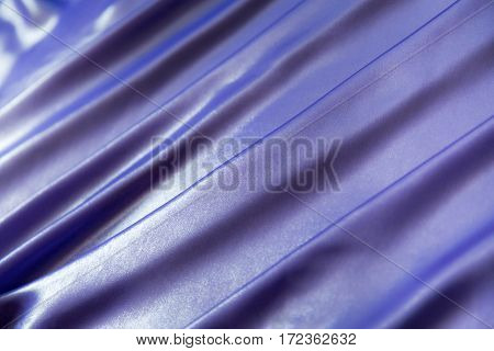 ackground of purple, blue shiny fabric, folded pleats