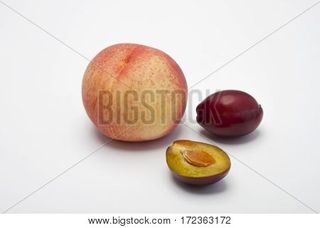 Peach and plum on a white background. Juicy peach and juicy plum