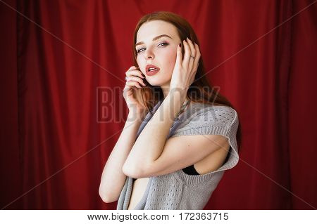 Beautiful red-haired girl with parted lips in black lingerie with necklace around her neck on red background looking at the camera. Fashion photography. Bright appearance. Red hair. Woman posing hands