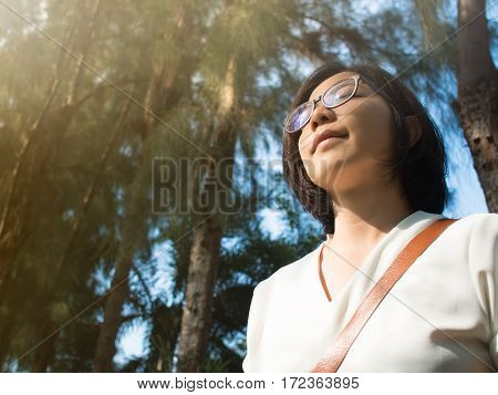 Beautiful young Asian woman relaxing and breathing in fresh air in autumn.