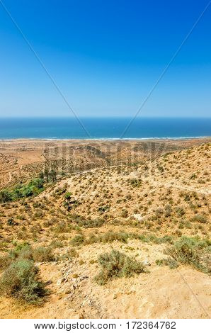 Beautiful view on oceanic beach from a high hill in Morocco in summer. Road serpentine goes towards the ocean