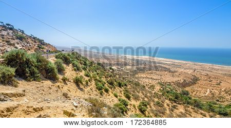 Beautiful view on oceanic beach from a high hill in Morocco in summer. Road serpentine goes towards the ocean. Panorama shot