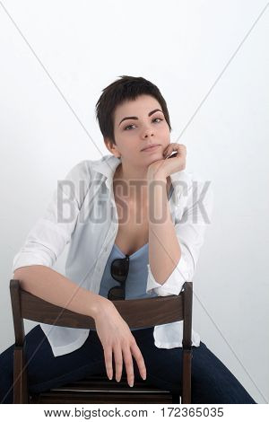 Young beautiful sexy smiling girl in shirt sitting on chair isolated on the white background, looking at the camera.