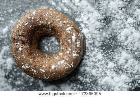 Close up of donuts with icing. Top view of chocolate donuts with icing sugar on black wooden background. Flat lay donuts.