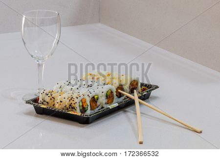 Portion Of Sushi On Tray, Chopsticks And Glass For Wine