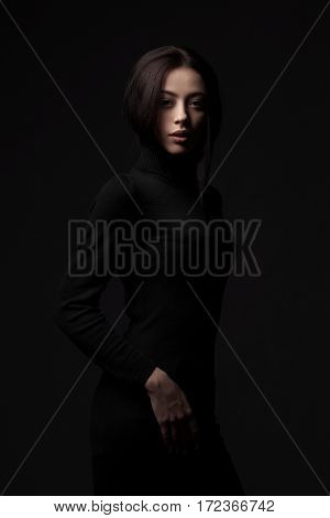 portrait of young elegant woman wearing black dress on black background. Fashion studio shot.