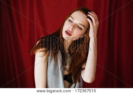 Beautiful red-haired girl with parted lips in black lingerie with necklace around her neck on red background looking away. Fashion photography. Bright appearance. Red hair. Woman posing hands