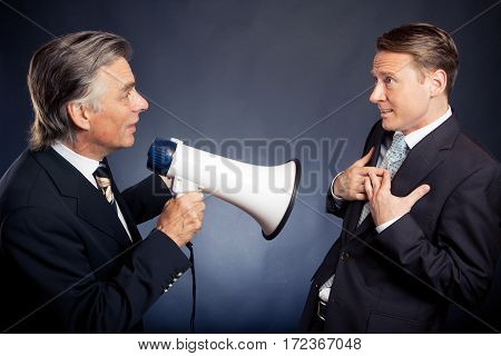 studio shot of a senior businessman shouting at his employee