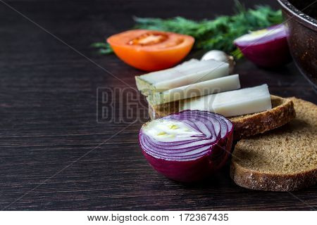Ukrainian national food is lard (salo) with bread with red onions on the background of the tomato with garlic on wooden table