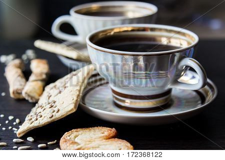Two cups of coffee with puff pastries with sunflower seeds sesame seeds and flax.Small depth of focus.