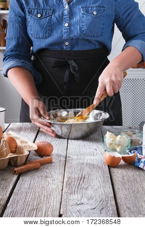 Baking concept. Flour, milk, butter, yeast, spices and eggs carton on rustic wooden table, cooking ingredients. Cropped image of unrecognizable woman stir dough. Female chef baker at cooking classes