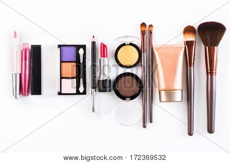 Makeup cosmetics, brushes and other essentials row on white background. Top view, flat lay. Multicolored beauty tools collection, lipsticks, eyeshadow, mascara, lip balm and more