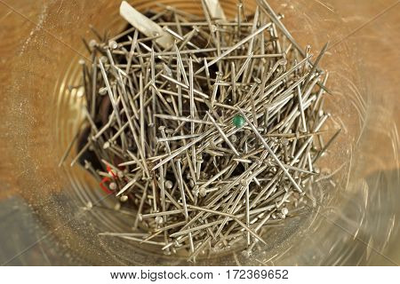 Glass container with a heap of silver pins used in clothing (garment) industry on the wooden background as a symbol of handmade sewing, fashion and manufacturing