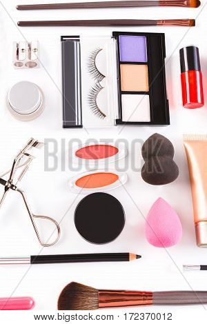 Makeup cosmetics, brushes and other essentials on white background. Top view, flat lay. Multicolored beauty tools and products collection, lipstick, eyeshadow, pencil, sponge, eyelash curler