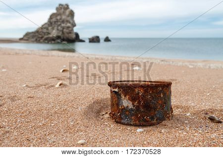Rusty tin can on beach - concept of environment background