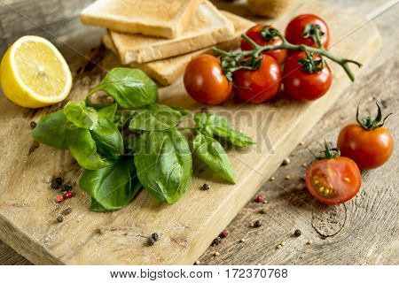 basil and cherry tomatoes branch with a lemon on a wooden board on a background of toast