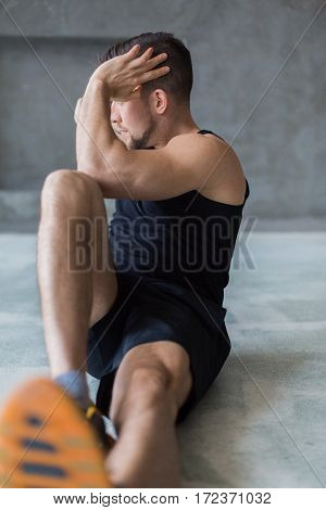 Young man workout in fitness club. Closeup portrait of caucasian guy making exercise, sit-ups and cross crunches for abs muscles, training indoors. Vertical