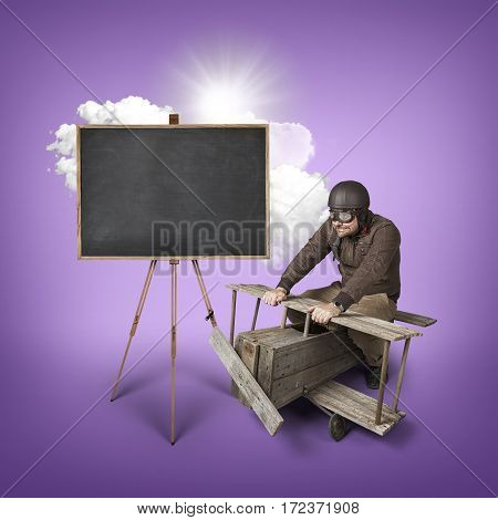 Blank blackboard with businessman and wooden aeroplane on color background