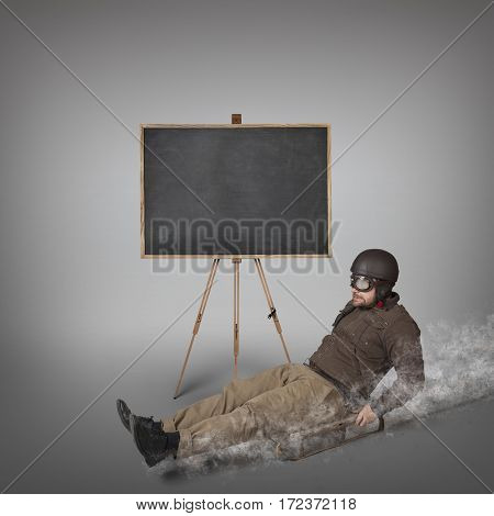 Empty blackboard with businessman sliding with a sledge indoor