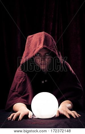 Studio shot of spooky fortune teller with crystal ball