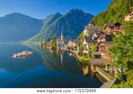 Scenic picture-postcard view of famous Hallstatt mountain village in the Austrian Alps with passenger ship in beautiful morning light on a sunny day in summer Salzkammergut region Austria