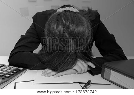 Stressed businesswoman bend down the head or sleep at her desk overwork black and white concept