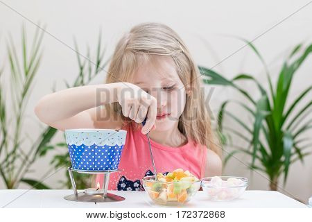 Little Girl Preparing And Eating A Chocolate Fondue.
