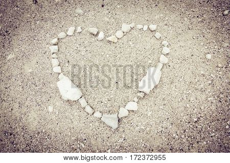 pebbles aranged on the ground in a heart shape