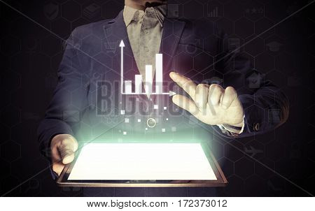 Image of a man with a tablet in his hands. He presenting a financial analysis using chart. Concept business analytics online.