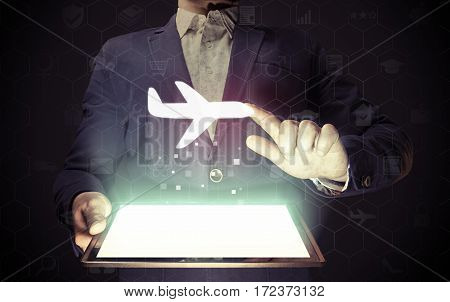 Image of a man with tablet in his hands with aircraft icon. Buying or booking online ticket. Travel concept business flights airplane delivery of cargoes and goods logistics.