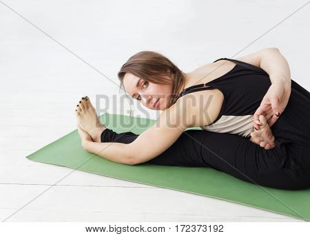 Seated Forward Bend. Intense Dorsal Stretch Girl Is Doing Yoga While Holding A Difficult Asana