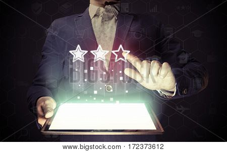 Concept of online rating. Man touches to the three stars (rating icon). He holds tablet pc that contains a many different online services.