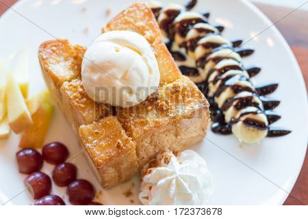 Honey toast with vanilla ice cream whipped cream and chocolate syrup. Served with banana grape and apple(selective focus)