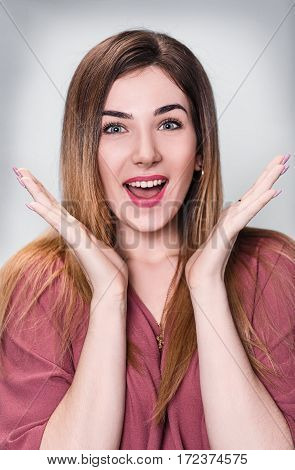 Beautiful excited smiling woman with open mouth and open palms over gray background.