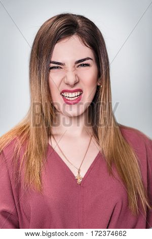 Portrait of angry young woman over gray background