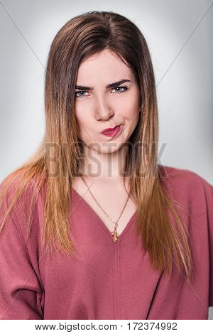 Portrait of displeased young woman over gray background