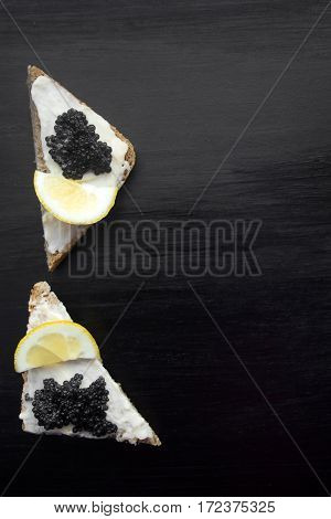 canapes with black caviar on a black background